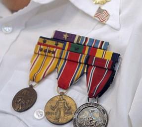 Marine Sgt. Thomas P. Smith pins Glenn Buzzard of Hubbard during a service honoring vets at Windsor House at Liberty Arms.