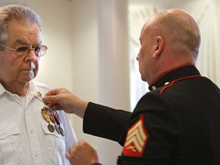 Marine Sgt. Thomas P. Smith pins Glenn Buzzard of Hubbard during Crossroads Hospice's service honoring vets  at Windsor House at Liberty Arms.