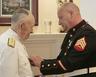Sgt. Thomas P. Smith pins Admiral Kenneth Monroe during Crossroads Hospice service honoring vets at Windsor House at Liberty Arms.