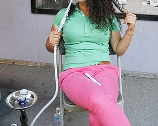MADELYN P. HASTINGS | THE VINDICATOR..Rena Mansour of New Castle, PA smokes hookah at the Arab American Community Festival in downtown Youngstown on Saturday, August 24, 2013.... - -30-..