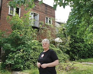 Jan Pentz of Youngstown's North Side stands in front of two houses on the 1300 block of Wick Avenue that are in need of demolition. Pentz lives across the street from the structures.