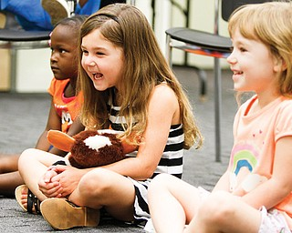 "Children attending a Tales and Tots literacy program at the Newport branch of the Public Library of Youngstown and Mahoning County show their smiles in the recent session that focused on repetitious use of the letter ""D."" From left are Brazil Moore, 3; Halo Fellows, 4 1⁄2; and Nina Hudock, 4. Selena Phillips, a children's librarian, said the program used music, movements and stories to enhance an appreciation for reading."