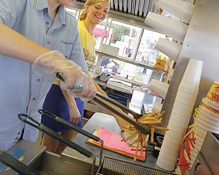 Vindicator reporter Kalea Hall tries her hand at cooking french fries at a Molnar's stand at the Canfield Fair. Molnar's has 12 concession stands and has been at the fair for 45 years.