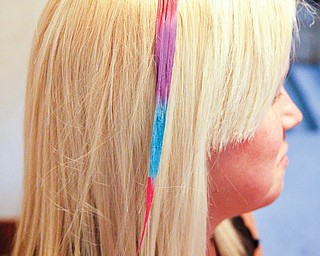 Wrobel's blond hair is highlighted with bright colors after Myers applied special chalk to it. The temporary color can be used on strands of hair from crown to ends or just on the tips of hair.