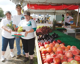 One of the staples at the Canfield Fair is Guzzo's Fruit Stand on Bishop Street. Showing off some of the produce fairgoers can buy are, from left, Christina Guzzo, Bill Welsh and Ella Maria Guzzo-Welsh.
