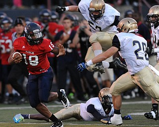 Fitch #18 Antwan Harris prepares to stiff arm Hoban defender #28 Joe Parisi after sprinting past a hurdling #52 Max Zoldesy during the first quarter of a game on Friday September 6, 2013.
