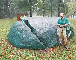 Mill Creek Park naturalist Ray Novotny stands next to Council Rock in Lincoln Park on Youngstown's East Side. Novotny will lead a hike Sunday in the Dry Run creek gorge from the park to the Lake McKelvey dam and back. Legend has it that hundreds of Native Americans who had gathered for a conference at the rock in 1755 were killed by a lightning strike that split the granite rock.