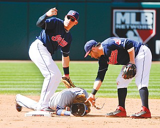 The Indians' Asdrubal Cabrera waves for help as Jason Kipnis picks up the helmet of Mets base runner Justin