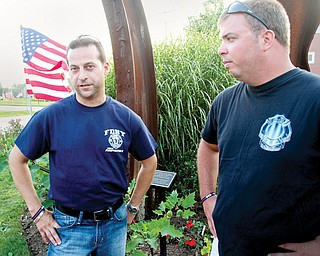 New York Fire Department members Nick Mincone, left, and Mike Kahlua look over a memorial at the Austintown 9/11 Memorial Park. The two will speak at Austintown's 9/11 ceremony at 6 p.m. today.