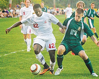 Cardinal Mooney's Justin Parkins (42) runs with the ball while Ursuline's Justin Oaks (23) attempts to steal it during a match Tuesday at the James Simon Sr. Soccer Park in Struthers. The Cardinals beat the Fighting Irish, 2-0.