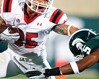 Youngstown State's Jamaine Cook, left, stiff -arms Michigan State's Johnny Adams during a game in East Lansing, Mich. Michigan State won, 28-6. The teams will meet again Saturday in East Lansing.
