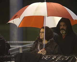 Lynn, left, and Randy Beatty, from Lowellville, try to stay dry Friday night while watching the Rockets at Springfield High School.