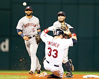 Houston Astros second baseman Jose Altuve throws over Cleveland's Nick Swisher (33) to complete a double play on a ball hit by the Indians' Jason Kipnis in the third inning of a game Thursday in Cleveland. The Indians won 2-1 in 11 innings.