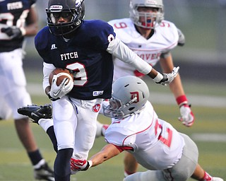 Fitch running back #9 Joey Harrington attempts is tripped up by Dover defensive back #2 Brian Pressley after breaking into the secondary in the first quarter.