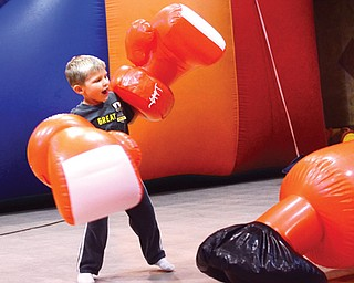 """Ryan Gray wears mega-size boxing gloves to punch a big bag at a recent fun day kick-off for Promiseland Children's Ministry at Wedgewood Park Church, 1944 S. Meridian Road, Austintown. The 4-year-old was with his grandfather, Bob Gray, who said, """"He's having a blast."""""""