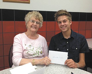 SPECIAL TO THE VINDICATOR Austintown Growth Foundation awarded a scholarship to Brandon Fisher, above, at a recent foundation meeting. He is studying math at Youngstown State University. Presenting a check is Joyce Pogany. Fisher took honors courses at Fitch High School and played varsity tennis. He works at his church and plays guitar with his friends. His local band has won two Indie Music Channel awards.