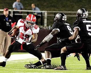 Youngstown State's Martin Ruiz puts a move on Southern Illinois' Bryan Presume (9) and Southern Illinois' Terrell Wilson during the second half of the Salukis' 28-27 loss to the Penguins at Saluki Stadium on Saturday, Sept. 28, 2013, in Carbondale, Ill. (Paul Newton / The Southern)