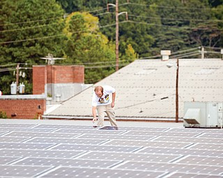 Mike Easterwood checks one of the solar panels installed on the roof of his 1947-era building in Decatur, Ga. Easterwood paid about $320,000 to install nearly 400 solar panels on top of his self-storage business near Atlanta.
