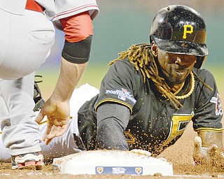 The Pirates' Andrew McCutchen dives back to first on a pickoff attempt in the fourth inning of the NL wild-card game against the Cincinnati Reds on Tuesday night. The Pirates won, 6-2.