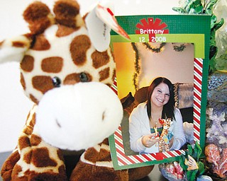 A photo of Brittany Mowry is attached to a stuff ed giraffe, her favorite animal. Brittany died Aug. 3 of cystic 