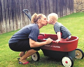 Colton, 2, gives Aunt Laurie a kiss for giving him wagon rides in the backyard while she was visiting him in Arlington, Texas.