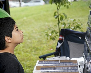 MADELYN P. HASTINGS | THE VINDICATOR..Jacob Wolf, 9, of Boardman, looks at comic book collectables at the fourth annual Lawn-Con on the west side on Saturday, October 5, 2013. ... - -30-..