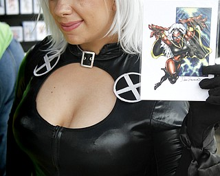 MADELYN P. HASTINGS | THE VINDICATOR..Stephanie Karasevich of Cleveland, dressed as X-Men's Storm, poses with a Storm character collectable card at the fourth annual Lawn-Con on the west side on Saturday, October 5, 2013. ... - -30-..