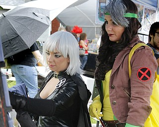 MADELYN P. HASTINGS | THE VINDICATOR..(L-R) Stephanie Karasevich, dressed as X-Men's Storm, and Riley Rivera, dressed as X-Men's Rogue, both of Cleveland, look at comic book collectables at the fourth annual Lawn-Con on the west side on Saturday, October 5, 2013. ... - -30-..