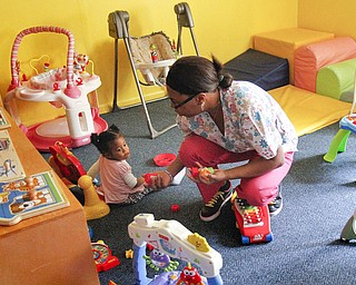 MADELYN P. HASTINGS | THE VINDICATOR..Vonetta Davis plays with 1 year old Alexia Moorer in Banana Darlings Learning Center on YoungstownÕs East Side. Davis has worked with children for more than 20 years, but this is her first business venture. .... - -30-..