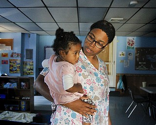 MADELYN P. HASTINGS | THE VINDICATOR..Vonetta Davis holds 1 year old Alexia Moorer in Banana Darlings Learning Center on YoungstownÕs East Side. Davis has worked with children for more than 20 years, but this is her first business venture. ... - -30-..