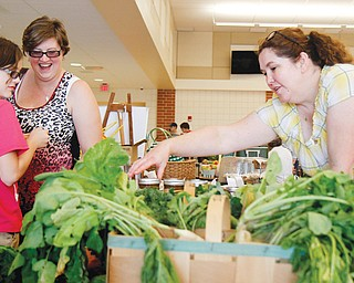 Mackenzie, 10, left, and Courtney Kuhns of Austintown admire the goods at Bridget Harker's farmers' market booth set up inside Austintown Intermediate School for the Awesometown event Sunday.