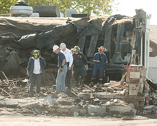 Boardman Fire Chief George D. Brown, in white shirt, arson investigators and investigators from the state fire marshal's office sift through the rubble after a fire at the Spice of India restaurant on Market Street.