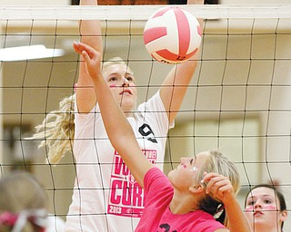 Springfield's Marissa Buchenic (21) and East Palestine's Carley Sansenbaugher (9) battle at the net during a volleyball match Tuesday night at Springfield. The host Tigers beat the Bulldogs, 25-21, 25-8, 25-17.