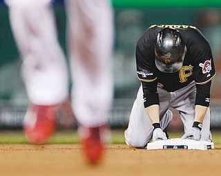 The Pirates' Clint Barmes kneels on second base after being forced out on a double play to end the sixth inning of Game 5 of the National League Division Series against the St. Louis Cardinals on Wednesday at Busch Stadium in St. Louis. The Pirates' storybook season came to an end in a 6-1 loss to the Cardinals. St. Louis will face the LA Dodgers in the championship series, which begins Friday in St. Louis.