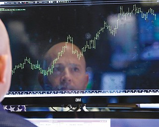 Specialist Jay Woods is reflected in a screen at his post on the floor of the New York Stock Exchange on Thursday. Wall Street roared in approval Thursday after Washington appeared to break an impasse that threatened to push the country into default.