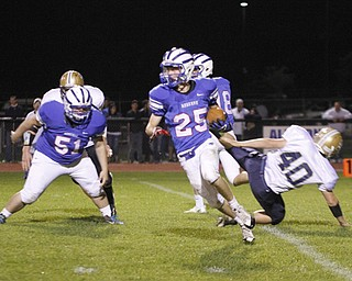.          ROBERT  K. YOSAY | THE VINDICATOR..WR  #25  Brian Sunderman  leaves #40 lowellville  Evan Amos as #51 WR  R J Jones watch as he goes for a first down.Lowellville at Western Reserver