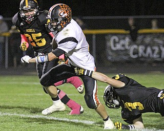 Ryan Kohler (11) of Springfield breaks through a shoe string tackle by Spencer DeSalvo (3) of Crestview during the second quarter of Friday nights matchup at Crestview High School.  Dustin Livesay  |  The Vindicator  10/11/13 Crestview High School.
