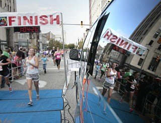 .          ROBERT  K. YOSAY | THE VINDICATOR..Mirror finish.. two runner s cross the line with the reflection in the glass..The 39th Annual Peace Race -  with over 2000 runners on a beautiful October day