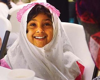 Zainab Rehman, 4, of Boardman, is excited as her mother puts on the scarf she purchased for her at an open house at the Masjid Al-Khair mosque in Youngstown on Sunday. The open house was the mosque's fifth and showcased a variety of ethnic foods, customs and information on Islam.