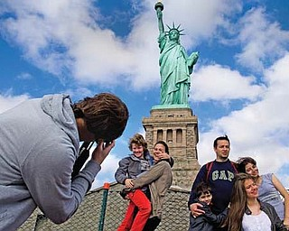 Tourists pose for photographs in front of the Statue of Liberty in New York Harbor on Sunday in New York. The Statue of Liberty reopened to the public after the state of New York agreed to shoulder the costs of running the site during the partial federal-government shutdown.