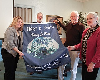 Members of the Friends of Mary B. Smith Committee, from left, Kristen Olmi, Rick Shale, Jim Ray and Judith Stanger, show the banner that will be displayed on the landing of the main stairway from DeBartolo Hall's second floor to the lobby in the College of Liberal Arts and Social Sciences at Youngstown State University.