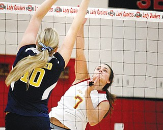 At left, United's Taylor John (10) tries to keep Cardinal Mooney's Jaclyn Yankle (7) from spiking the ball during