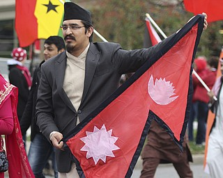 Youngstown State senior Arbin Shrestha carries the Nepal flag while walking with the international students during the Homecoming parade on Fifth Ave. in Youngstown on Saturday. Dustin Livesay  |  The Vindicator 10/19/13  Youngstown.