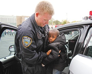 Youngstown State University police officer Mark Menley helps 2- year-old Da'Reion Solomon of Youngstown get out of a police cruiser at the Neighborhood Harvest. The festival was sponsored by ICU Block Watch, St. Dominic Church and Horizon Academy and featured music, treat bags with candy, Kids Identi-Kits and an inflatable