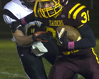 Kelli Cardinal/The Vindicator .South Range (#30) carries the ball Friday night and tries to avoid the tackle by Springfield (#86) at Memorial Field in North Lima.