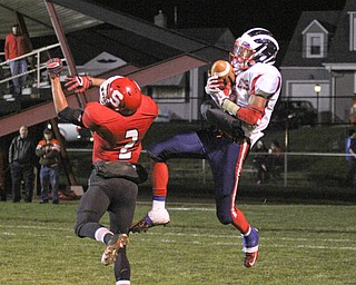 Niles McKinley's Marcus Hill (2) catches a touchdown pass over Frankie Serrano (2) of Struthers during the second quarter of Friday nights matchup at Struthers High School.  Dustin Livesay  |  The Vindicator 10/25/13  Struthers High School.