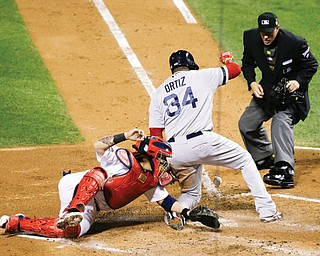 Home plate umpire Paul Emmel watches as Red Sox designated hitter David Ortiz slides safely past Cardinals catcher Yadier Molina on a sacrifice fly by Stephen Drew in the fifth inning of Game 4 of the World Series on Sunday in St. Louis. The Red Sox slipped by the Cardinals to win 4-2 and tie the series at 2-2.