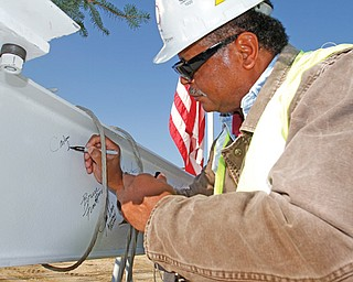 Carlton Ingram, Local 66 operating engineers business manager, signs a steel beam before it was placed on the main building at the Hollywood Gaming at Mahoning Valley Race Course site in Austintown on Tuesday.