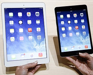 An Apple employee demonstrates the new iPad Air, left, and iPad mini in San Francisco. Analysts say the iPad is facing its stiffest holiday-season competition since its 2010 introduction.