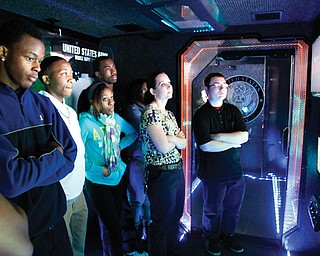Students at in the Science, Technology, Engineering and Mathematics program at Youngstown's Chaney Campus, Bryan Moncrief, from left, Omon'dre Moncrief, Sydney McIntyre, Jeremy Woodberry, teacher Carrie Sinkele and Ken Bossick watch a scenario on a screen inside the Army STEM Asset Vehicle, which visited Chaney on Thursday.